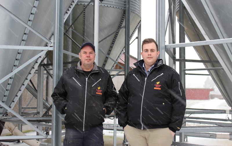 Två personer framför silos
