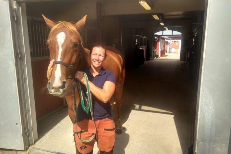 Kvinna med häst i stall