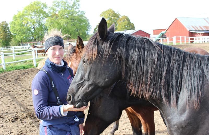 Bild på travtränaren Anna Forssell ståendes vid hennes hästar
