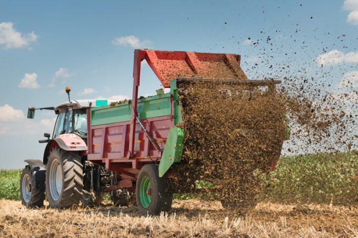Traktor som gödslar ett fält