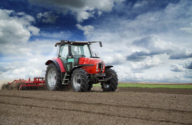 En röd traktor på åker med harv