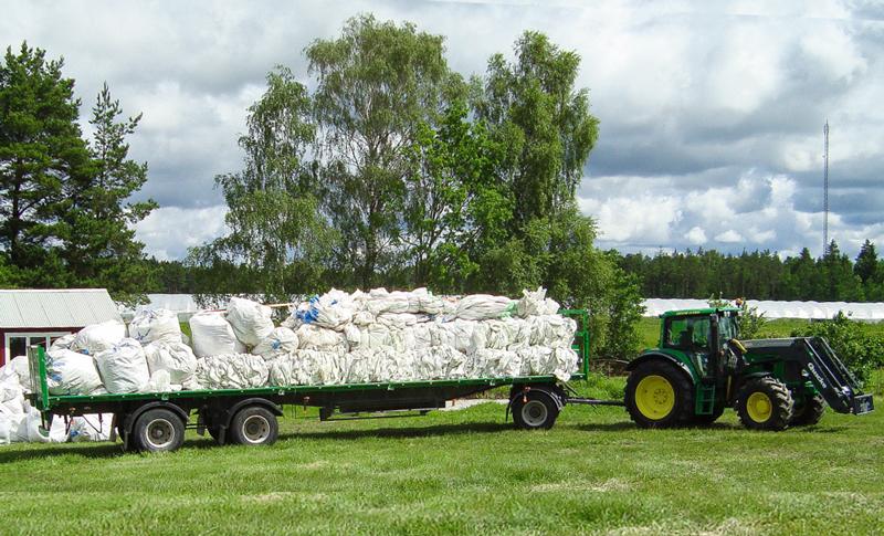Traktor med ett flak medplastsäckar