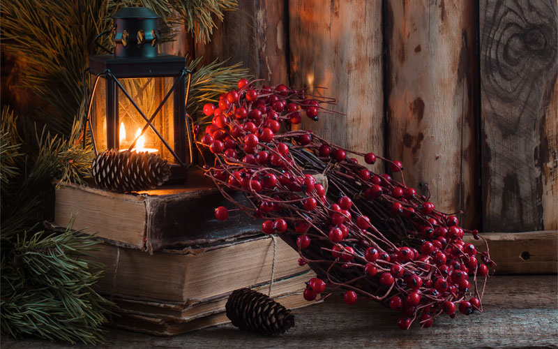 Lyckta med julkrans framför en trävägg